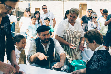PUERTOMINGALVO, TERUEL, SPAIN - AUGUST 5, 2018: Group of men and women making handcraft sausage during an exhibition celebrated in a medieval fair in Puertomingalvo, a small town located in the Maestrazgo Cultural Park in the region of Gudar Javalambre, i Editorial