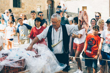 PUERTOMINGALVO, TERUEL, SPAIN - AUGUST 5, 2018: Middle aged man is making a pork meat auction in a medieval fair celebrated in Puertomingalvo, a small town located in the Maestrazgo Cultural Park in the region of Gudar Javalambre, in the province of Terue