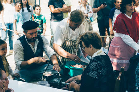 PUERTOMINGALVO, TERUEL, SPAIN - AUGUST 5, 2018: Group of women and men making handcraft sausage during an exhibition in a medieval fair celebrated in Puertomingalvo, a small town located in the Maestrazgo Cultural Park in the region of Gudar Javalambre, i Editorial