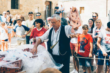 PUERTOMINGALVO, TERUEL, SPAIN - AUGUST 5, 2018: Old man is making a pork meat auction in a medieval fair celebrated in Puertomingalvo, a small town located in the Maestrazgo Cultural Park in the region of Gudar Javalambre, in the province of Teruel, Arago Editorial