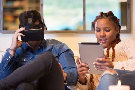 Couple of friends, a young caucasian man is using virtual reality glasses and a young mixed race woman is using a tablet sitting in a sofa at home.