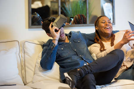 View of a happy couple of friends, a young caucasian man is using virtual reality glasses and a young mixed race woman is using a tablet sitting in a sofa at home. Фото со стока