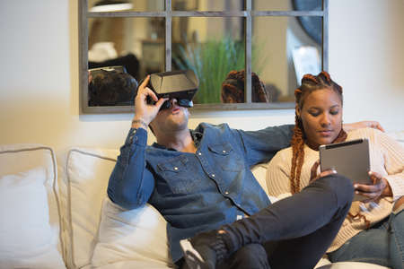 View of a young couple of friends, a caucasian man is using virtual reality glasses and a mixed race woman is using a tablet sitting in a sofa at home. Фото со стока