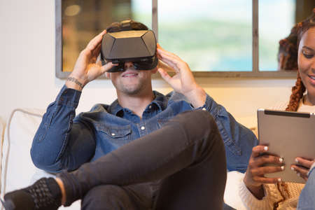 Front view of a couple of friends, a young caucasian man is using virtual reality glasses and a young mixed race woman is using a tablet sitting in a sofa at home.