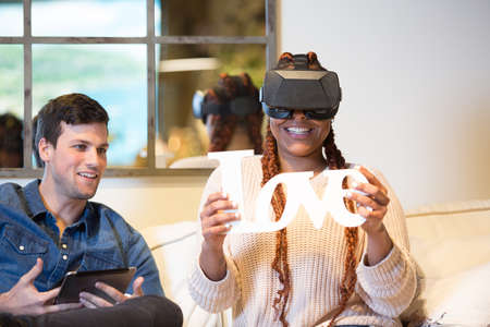 Smiling couple of friends, a young mixed race woman using virtual reality glasses and a young caucasian man is using a tablet while are sitting in a sofa at home.