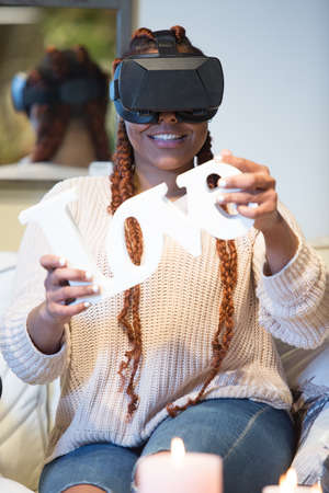 Smiling young woman is using virtual reality glasses and she is having fun seated in the sofa at home.
