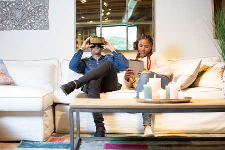 View of a couple of friends, a young caucasian man using virtual reality glasses and a young mixed race woman is using a tablet sitting in a sofa at home.