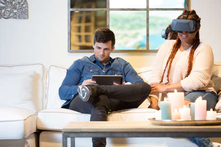 Couple of friends, a young mixed race woman is using virtual reality glasses and a young caucasian man is using a tablet sitting in a sofa at home.