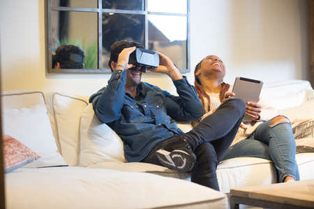 View of a smiling couple of friends, a young caucasian man is using virtual reality glasses and a young mixed race woman is using a tablet sitting in a sofa at home. Фото со стока