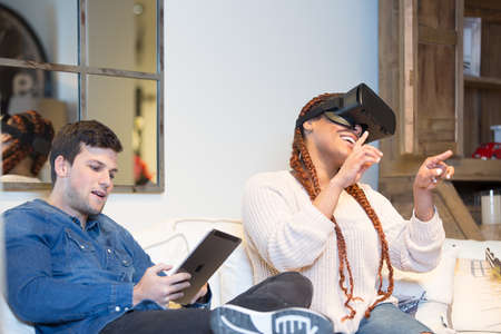 Couple of friends, a happy young mixed race woman uses virtual reality glasses and a young caucasian man is using a tablet while are sitting in a sofa at home. Фото со стока