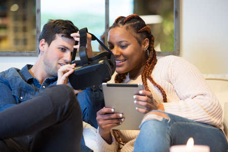 View of a smiling young couple of friends, a caucasian man and a mixed race woman using virtual reality glasses and a tablet sitting in a sofa at home.