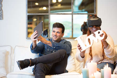 Smiling couple of friends, a young mixed race woman uses virtual reality glasses and a young caucasian man uses a tablet while are sitting in a sofa at home.