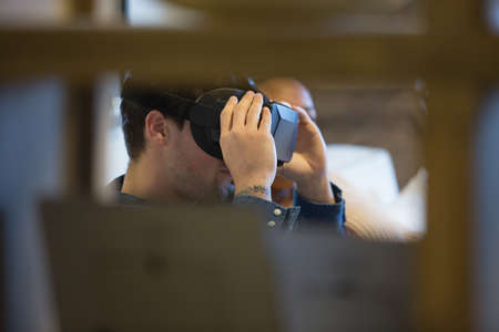 Cropped view of a young man is using virtual reality glasses at home.