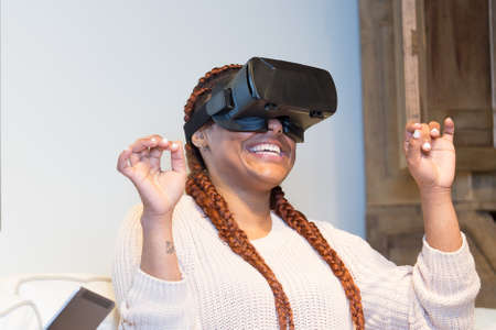 Happy young woman is using virtual reality glasses and she is having fun seated in the sofa at home. Stok Fotoğraf