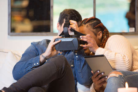 Young couple of friends, a caucasian man and a mixed race woman using virtual reality glasses and a tablet sitting in a sofa at home. Stok Fotoğraf