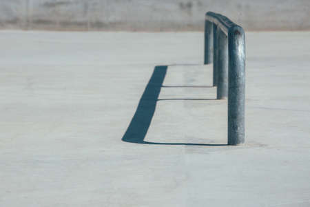 View of the detail of a railing used as an obstacle of an empty urban skate park. Useful as a background.