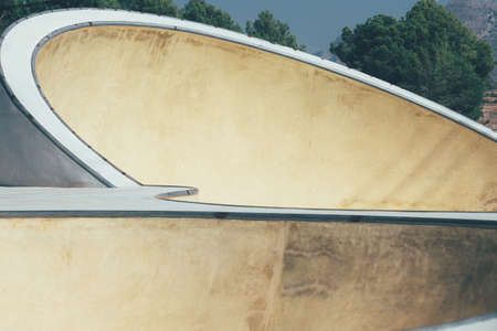 View of the detail of the bowls and ramps of an empty urban skate park. Useful as a background. Imagens