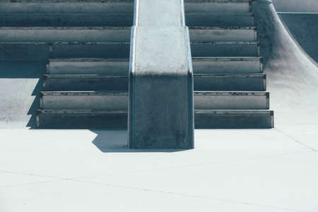 View of the detail of a ramp and the stairs used as obstacles of an empty urban skate park. Useful as a background. Imagens