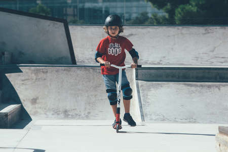 Front view of a young boy is wearing a helmet and the protections is using a scooter in an urban skate park. Stok Fotoğraf