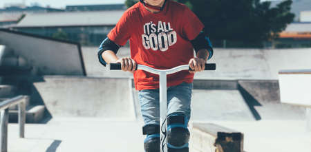 Cropped view of a young boy is wearing the protections is using a scooter in an urban skate park.