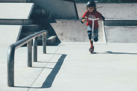 Front view of a young boy wearing a helmet and the protections is using a scooter in an urban skate park.
