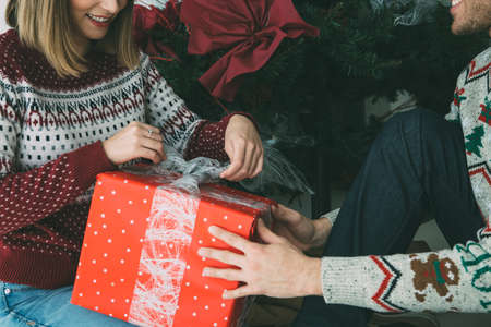 Cropped view of a young man is giving a Christmas gift to his smiling beloved woman under the fir tree and wearing Christmas sweaters Stok Fotoğraf