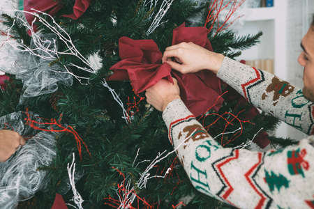 Cropped view of a young man and a young woman are decorating a fir tree with Christmas ornaments wearing Christmas sweaters
