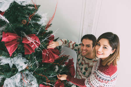 Top view of a smiling young woman and a young man are decorating a fir tree with Christmas ornaments wearing Christmas sweaters