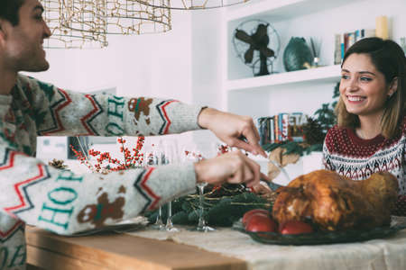 Smiling young woman and man are celebrating Christmas meal on a decorated table and a roasted turkey ready to be eaten Фото со стока