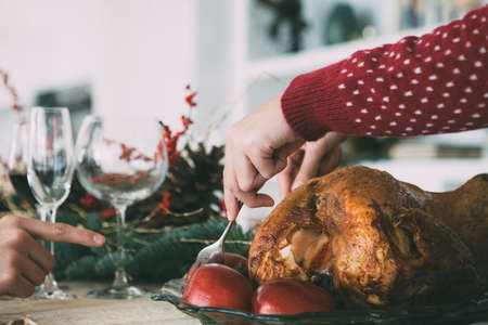 Cropped view of a the hands of a young woman carving a delicious roasted turkey on a Christmas table decorated