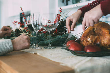 Cropped view of a the hands of a young woman carving a delicious roasted turkey on a Christmas table decorated and a young man with a glass of wine Фото со стока