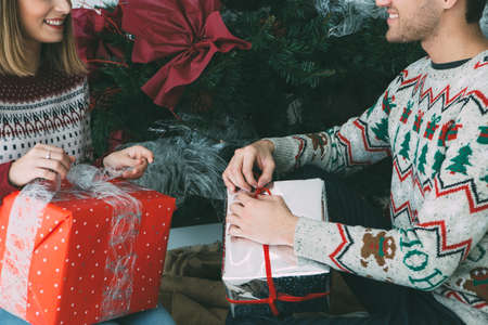 Cropped view of a smiling young man and woman are opening Christmas presents under the fir tree and wearing Christmas sweaters Фото со стока