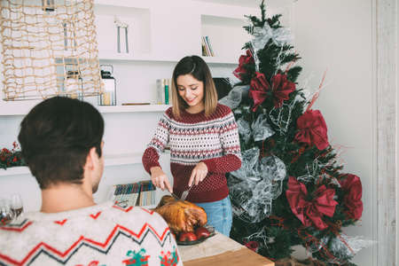 View of a young woman standing is carving a roasted turkey on a Christmas table decorated in front of her beloved man