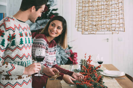 Smiling young woman is decorating a table with Christmas ornaments with a young man with a glass of wine in his hand Banque d'images - 116267437