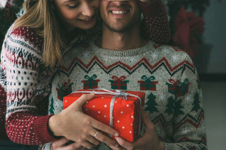Cropped view of a lovely young woman is giving a Christmas gift to her beloved man under the fir tree and wearing Christmas sweaters