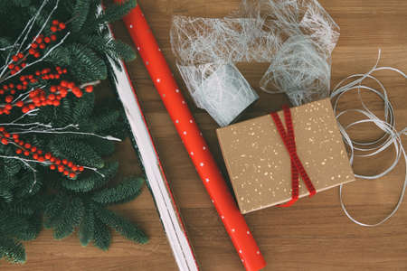 Top view of Christmas gift wrapping tools composed of wrapping paper, box and ribbons useful as a background. Imagens