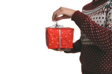 Cropped view of a young woman is holding a Christmas gift and she is wearing a Christmas sweater on a isolated white background. Copy space area available