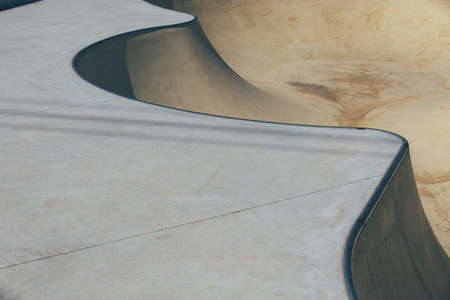 Detail of the ramps of a bowl used as an obstacle to make tricks in an empty urban skate park. Useful as a background.