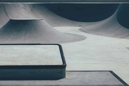 Detail of the obstacles to make tricks in an empty urban skate park as ramps, platforms. Useful as a background. Imagens