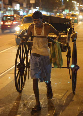 calcutta: Man pulling a traditional hand pulled rickshaw along a street in Calcutta West Bengal India