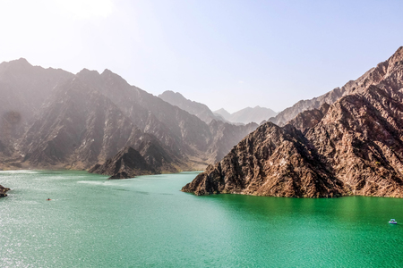 Geological landscape of hatta dam characterised by dry and rocky mountains and lake between scenery mountains, water reservoir Between hills in Dubai, United Arab Emirates