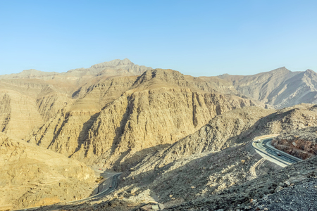 Geological landscape of Jabal Jais characterised by dry and rocky mountains, Road between mud mountains in Ras Al Khaimah, United Arab Emirates