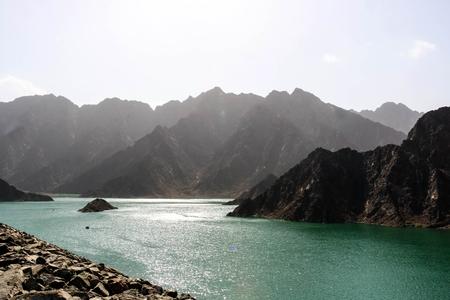 El paisaje geológico de la presa de Hatta se caracteriza por montañas secas y rocosas y un lago entre montañas de paisajes, depósito de agua entre colinas en Dubai, Emiratos Árabes Unidos.