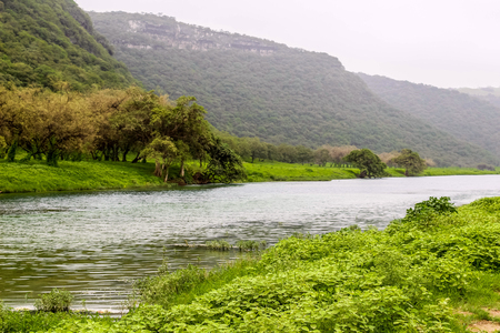 Waterfall in Ayn Khor and Lush green landscape, trees and foggy mountains at tourist resort, Salalah, Oman Stock Photo