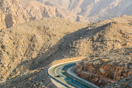 Geological landscape of Jabal Jais characterised by dry and rocky mountains, Road between mountains in Ras Al Khaimah, United Arab Emirates