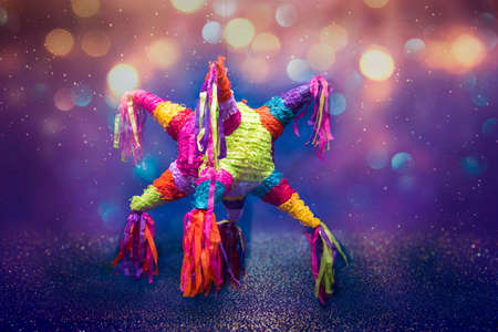 mexican piñata party hanging on blue and green background with multi-colored glitters celebrating birthday, christmas, party, party songs, figure in the shape of star and donkey, family fun Foto de archivo