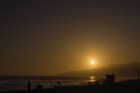 beack: Sunset with the Silhouette of a lifeguard tower at Sunset Beack in Malabu CA  Stock Photo