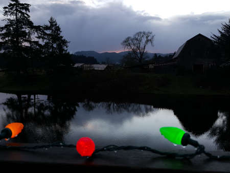 Christmas lights in front of pond and barn on CHristmas Morning Stock Photo