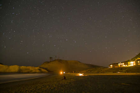 Night falls on Cape Kiwanda Oregon coast as friends enjoy a fire on the beach with the stars and hotel in the background.