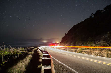 lights trail down road and curve on a cliff-side road next to the Pacific Ocean with the waves and stars in the background. Stock Photo